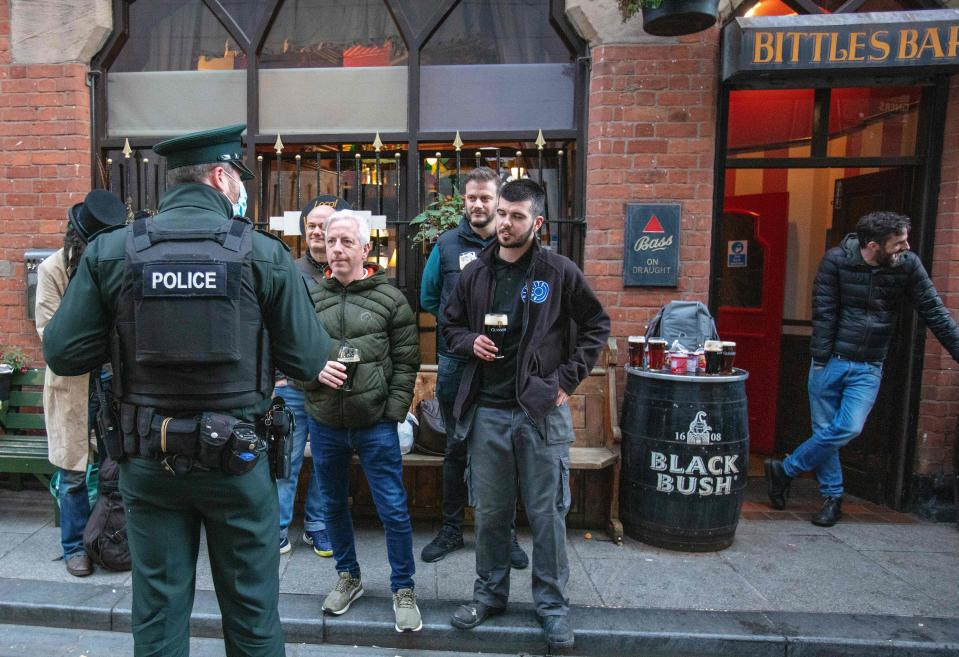 A police officer with bar patrons