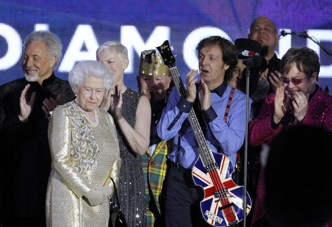 FILE - In this Monday, June 4, 2012 file photo, Britain's Queen Elizabeth II, 2nd from left, is joined on stage by performers Sir Tom Jones, Annie Lennox, Sir Paul McCartney and Sir Elton John at the conclusion of the Queen's Jubilee Concert in front of Buckingham Palace, London. McCartney turned 70 years of age Monday June 18, 2012. (AP Photo/Joel Ryan)