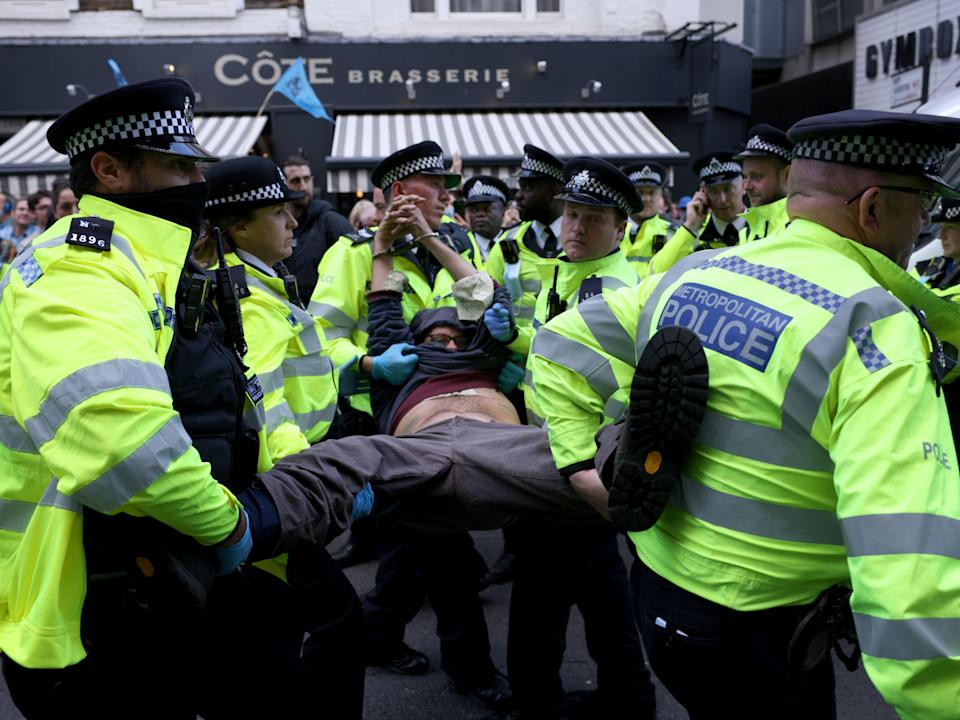 An XR protester, who installed himself on top of a van, is arrested at the group's first day of protesting in Covent Garden (Getty)