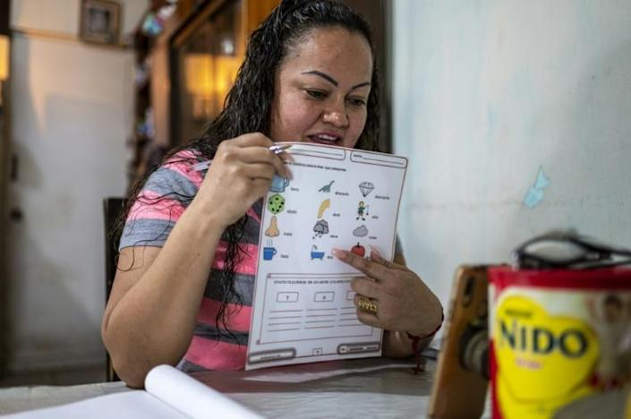 Alma Beatriz Serrano Ramirez points to a storm cloud on a chart during an online class she teaches from her home in Matamoros, Mexico on May 25, 2021