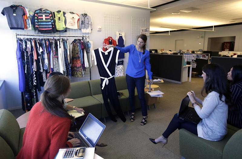 In this Sept. 18, 2013 photo, Andrea Rockers Wright, Walmart.com senior buyer for merchandise, center, shows clothing during a line review at the Walmart.com office in San Bruno, Calif. Wal-Mart has embraced a Silicon Valley startup feel with its San Bruno offices. That's a stark difference to the company's rambling brick headquarters with its frayed carpets and Seventies-style paneling. (AP Photo/Jeff Chiu)