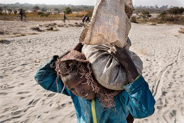 PHOTO: An undated photo shows Daniel, 11, carrying a bag of cobalt on his back in Kolwezi, D.R.C. He works in a mine ferrying sacks of cobalt to a depot.'n'nCobalt is a vital mineral needed for the production of rechargeable batteries. (Corbis via Getty Images, FILE)