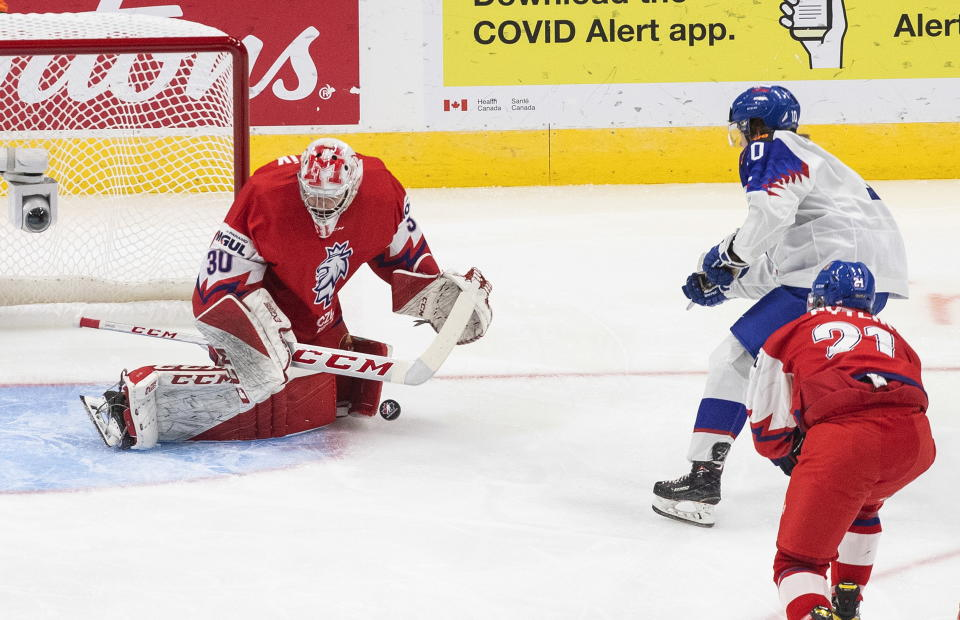 Czech Republic goalie Nick Malik (30) makes a save on Slovakia's Oleksij Myklucha (10) during the first period of a game leading up to the IIHF World Junior Hockey Championships, Wednesday, Dec. 23, 2020, in Edmonton, Alberta. (Jason Franson/The Canadian Press via AP)