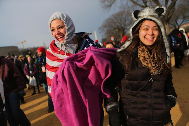 Susannah Ward (L) and Daniela Zara and others gather near the U.S. Capitol building on the National Mall for the Inauguration ceremony on January 21, 2013 in Washington, DC. U.S. President Barack Obama will be ceremonially sworn in for his second term today. (Photo by Joe Raedle/Getty Images)
