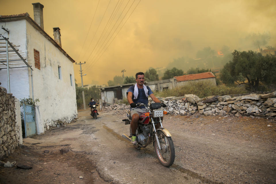 People move away from an advancing fire in Cokertme village, in Bodrum, Mugla, Turkey, Monday, Aug. 2, 2021. For the sixth straight day, Turkish firefighters were battling Monday to control the blazes tearing through forests near Turkey's beach destinations. Fed by strong winds and scorching temperatures, the fires that began Wednesday have left eight people dead and forced residents and tourists to flee vacation resorts in a flotilla of small boats.(AP Photo/Emre Tazegul)