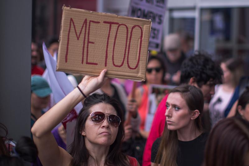 One woman holds a sign echoing the #MeToo social media campaign.