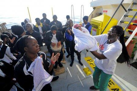 Migrants dance and sing to celebrate the birth of Miracle, a baby who was born on board the Aquarius, in the central Mediterranean Sea, May 26, 2018. REUTERS/Guglielmo Mangiapane
