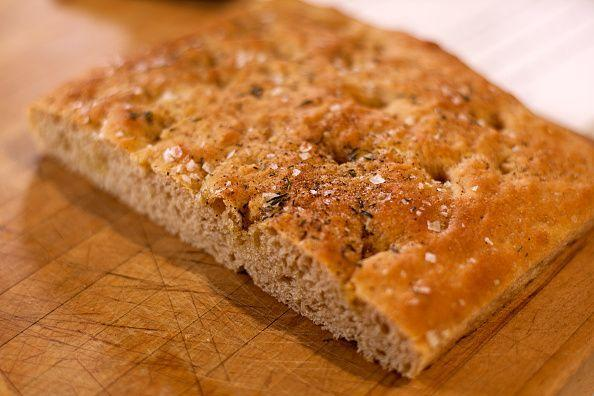 """<p><a href=""""https://www.delish.com/cooking/recipe-ideas/a25136571/focaccia-bread-recipe/"""" rel=""""nofollow noopener"""" target=""""_blank"""" data-ylk=""""slk:Focaccia"""" class=""""link rapid-noclick-resp"""">Focaccia</a> is an Italian bread typically baked flat, in a baking sheet or pan. The dough is similar to pizza dough, and is sometimes flavored with fresh herbs and garlic. Often it's coated with olive oil before baking for a distinctly delicate yet crunchy crust. It's often enjoyed on its own, but it's also great for dipping in soup or served with meat and cheese. </p><p>Try it in <a href=""""https://www.delish.com/cooking/recipe-ideas/recipes/a50180/apple-sausage-focaccia-stuffing-recipe/"""" rel=""""nofollow noopener"""" target=""""_blank"""" data-ylk=""""slk:Apple & Sausage Focaccia Stuffing"""" class=""""link rapid-noclick-resp"""">Apple & Sausage Focaccia Stuffing</a> from Delish.</p>"""