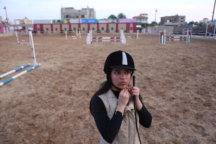 "Fatma Youssef, 17, a Palestinian high school student, adjusts her helmet as she prepares to ride a horse at an equestrian club in Gaza City on Dec. 9, 2018. ""I'm nervous because this is my final high school year, but when I ride my horse I become free of stress,"" Youssef said. (Photo: Samar Abo Elouf/Reuters)"