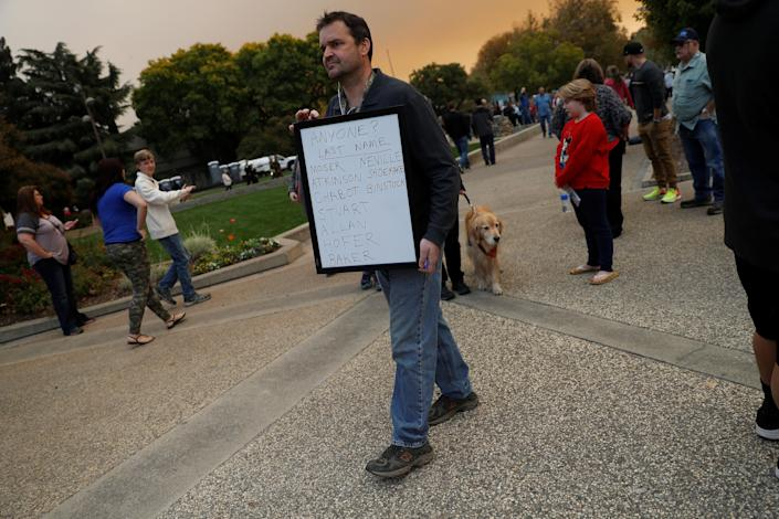 <p>Mark Leavenworth of the Oroville Nazarene Church holds a sign with names to help reconnect those displaced by the Camp Fire outside the emergency shelter at Neighbourhood Church of Chico in Chico, Calif., Nov. 11, 2018. (Photo: Stephen Lam/Reuters) </p>