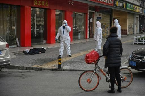 Officials in protective suits stand near an elderly man wearing a mask who collapsed and died on a street near a hospital in Wuhan