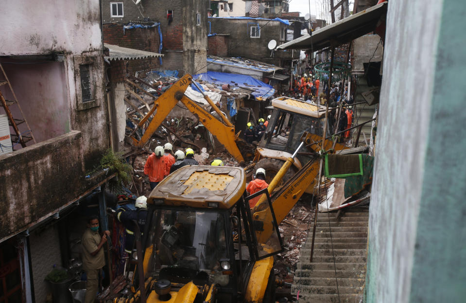 Rescuers clear the debris to find any residents possibly still trapped after a three-story dilapidated building collapsed following heavy monsoon rains n Mumbai, India, Thursday, June 10, 2021. (AP Photo/Rafiq Maqbool)