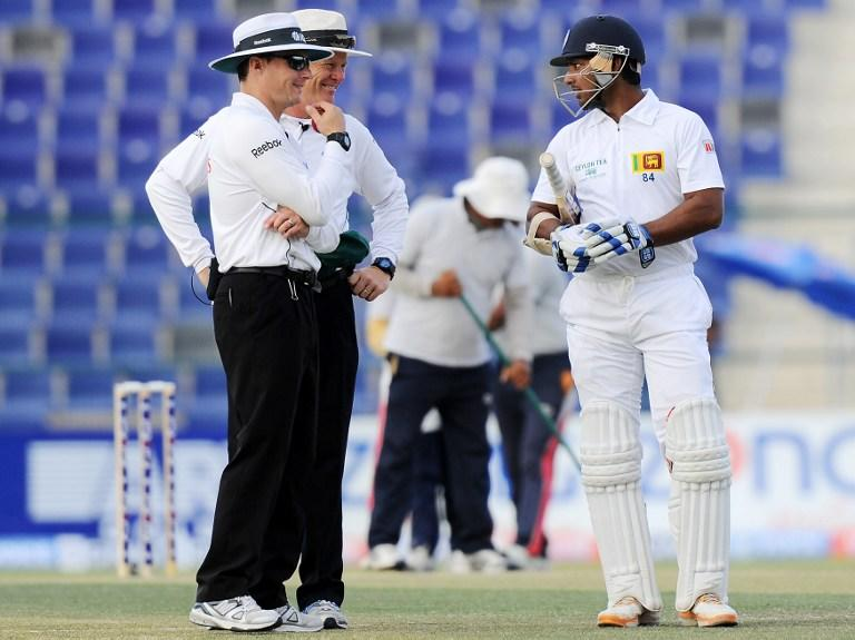 Sri Lankan batsman Kumar Sangakkara (R) speaks with umpires during the third day of the first cricket Test match between Pakistan and Sri Lanka at the Sheikh Zayed Stadium in Abu Dhabi on January 2, 2014. Pakistan's last six wickets fell cheaply on the third morning of the first Test and restrict them to 383. Sri Lanka's first-innings made 204 but they had to settle for a still-useful 179-run advantage. AFP PHOTO/Ishara S. KODIKARA