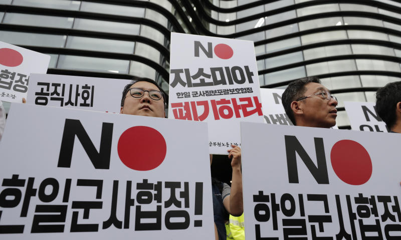 """In this Aug. 7, 2019, photo, South Korean protesters hold signs during a rally demanding the abolition of the General Security of Military Information Agreement, or GSOMIA, an intelligence-sharing agreement  between South Korea and Japan in front of the Japanese embassy in Seoul, South Korea. South Korea has threatened to end the military intelligence sharing agreement with Japan as their tensions escalate over export controls. The agreement, known as GSOMIA, is a symbol of the countries' trilateral security cooperation with their ally United States in the region. The letters read """"Abolition of the General Security of Military Information Agreement between South Korea and Japan."""" (AP Photo/Lee Jin-man)"""