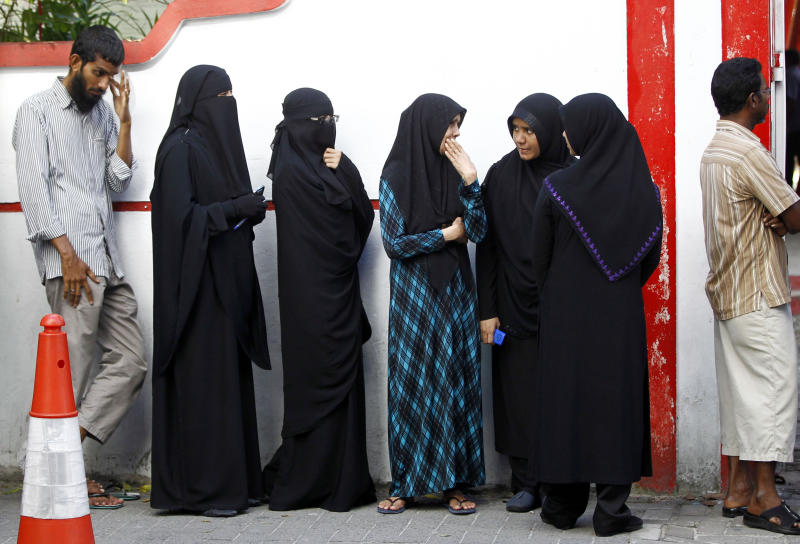 Maldivians stand in a queue to cast their votes in Male, Maldives, Saturday, Nov. 16, 2013. Voters in the Maldives lined up to cast their ballots Saturday in a presidential runoff that comes amid international concerns that the tiny archipelago nation may slip back to strongman rule after long delays in the election. (AP Photo/Sinan Hussain)