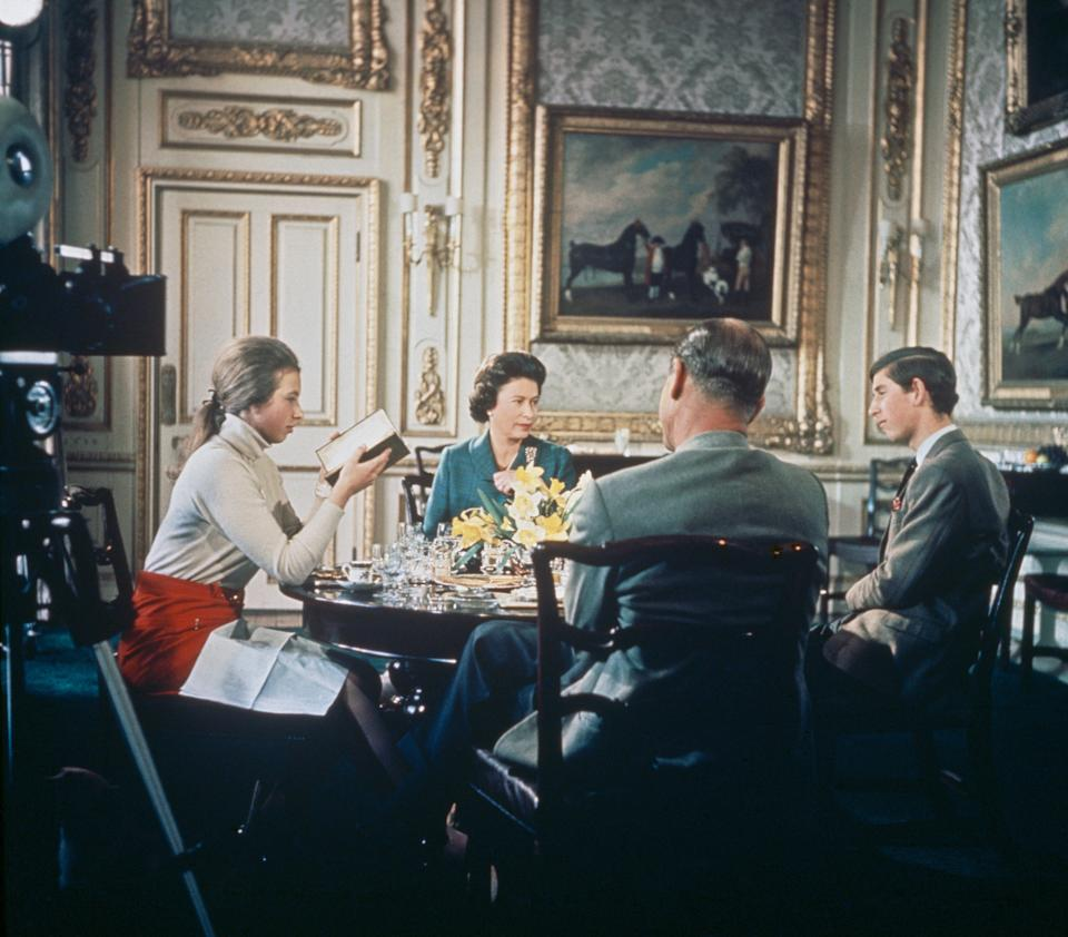 """Queen Elizabeth lunches with Prince Philip, Princess Anne and Prince Charles at Windsor Castle in Berkshire, circa 1969. A camera (left) is set up to film for Richard Cawston's BBC documentary """"Royal Family,"""" which followed the royals over a period of a year and was broadcast in June 1969."""
