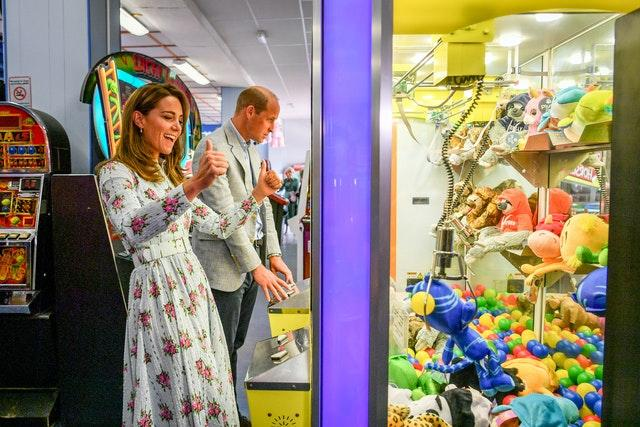 Kate's brief moment of excitement playing the claw game, before the soft toy is dropped