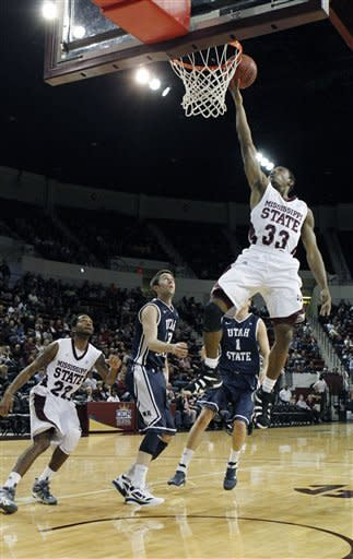 Mississippi State guard Deville Smith (33) makes a layup past Utah State guards Preston Medlin (13) and Ben Clifford (1) in the first half of their NCAA college basketball game in Starkville, Miss., Saturday, Dec. 31, 2011. (AP Photo/Rogelio V. Solis)