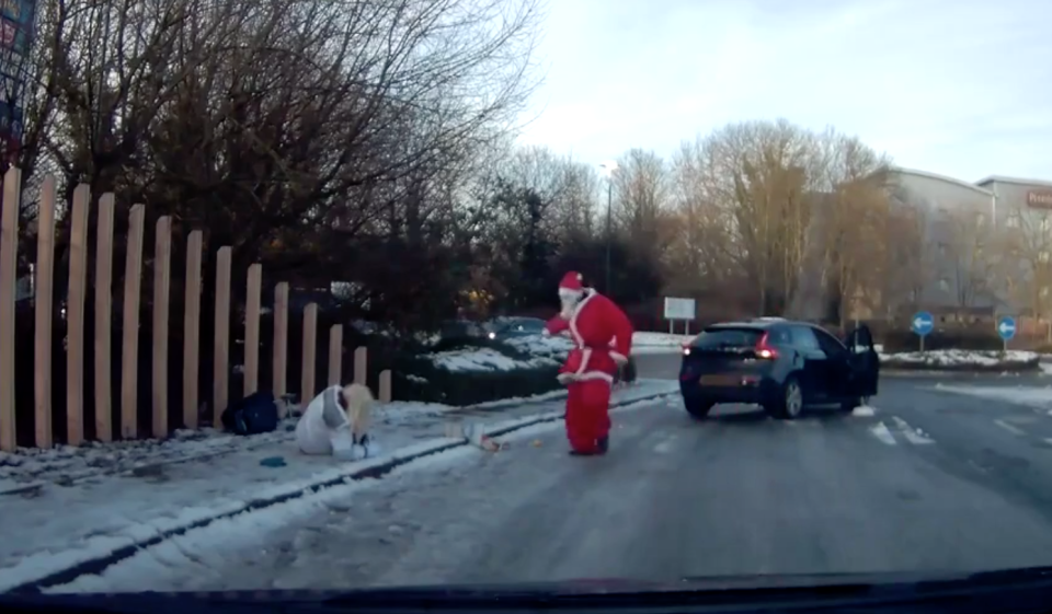 <em>Heroic rescue – When a pedestrian took a tumble on the ice, Santa himself hopped out of a car to rescue her (Pictures: Jukin Media)</em>
