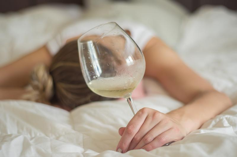 Great concept of alcohol abuse. Young woman, blond hair, fainted in bed after drinking too much alcohol. Glass of wine in hand, bottle of wine.