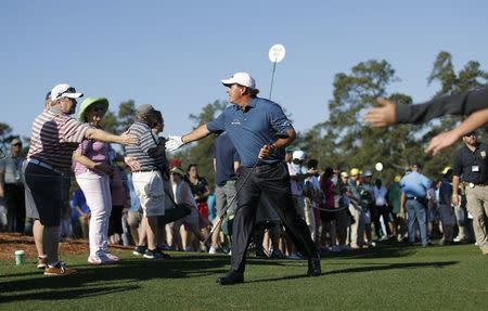 Phil Mickelson of the U.S. greets fans as he walks between the 7th and 8th holes during Tuesday practice rounds for the 2017 Masters at Augusta National Golf Course in Augusta, Georgia, U.S., April 4, 2017. REUTERS/Mike Segar