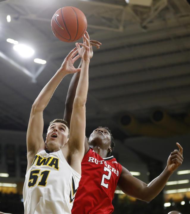 Iowa forward Nicholas Baer fights for a rebound with Rutgers center Shaquille Doorson, right, during the first half of an NCAA college basketball game, Saturday, March 2, 2019, in Iowa City, Iowa. (AP Photo/Charlie Neibergall)