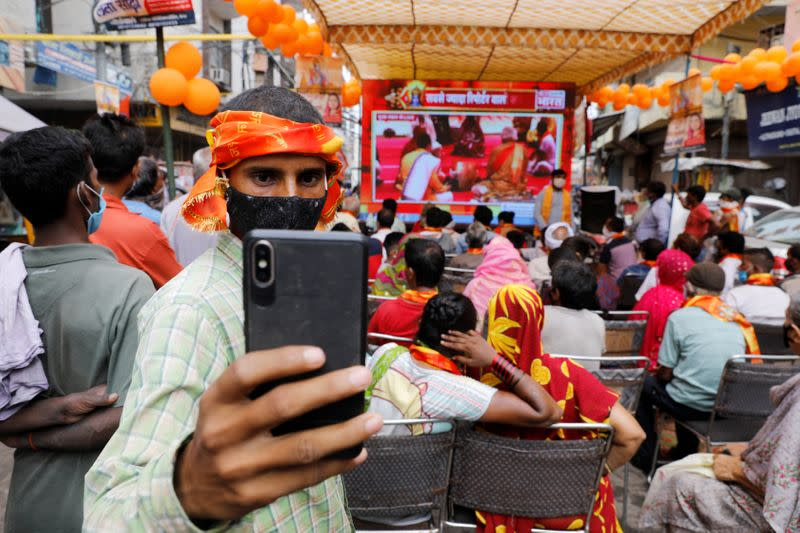 A Hindu man takes a selfie during a live screening of the stone laying ceremony of the Ram Temple by Prime Minister Narendra Modi in Ayodhya, in New Delhi