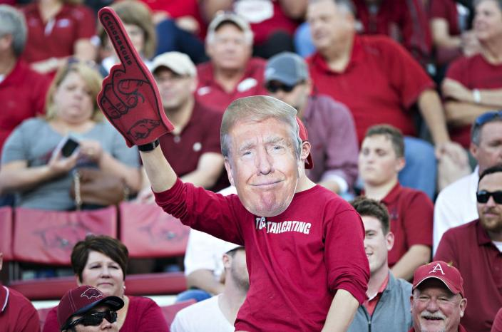 "<span class=""caption"">The lines between political fandom and sports fandom have blurred.</span> <span class=""attribution""><a class=""link rapid-noclick-resp"" href=""https://www.gettyimages.com/detail/news-photo/fan-of-the-arkansas-razorbacks-with-his-donald-trump-face-news-photo/615582270?adppopup=true"" rel=""nofollow noopener"" target=""_blank"" data-ylk=""slk:Wesley Hitt/Getty Images"">Wesley Hitt/Getty Images</a></span>"