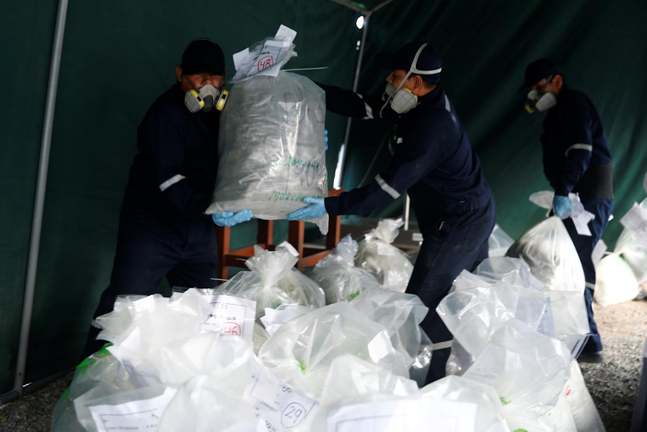Anti-narcotics workers carry bags containing cocaine and other drugs during the incineration of about 8 tons of drugs seized during police operations, according to the Interior Ministry, in Lima, Peru March 30, 2017. REUTERS/Guadalupe Pardo