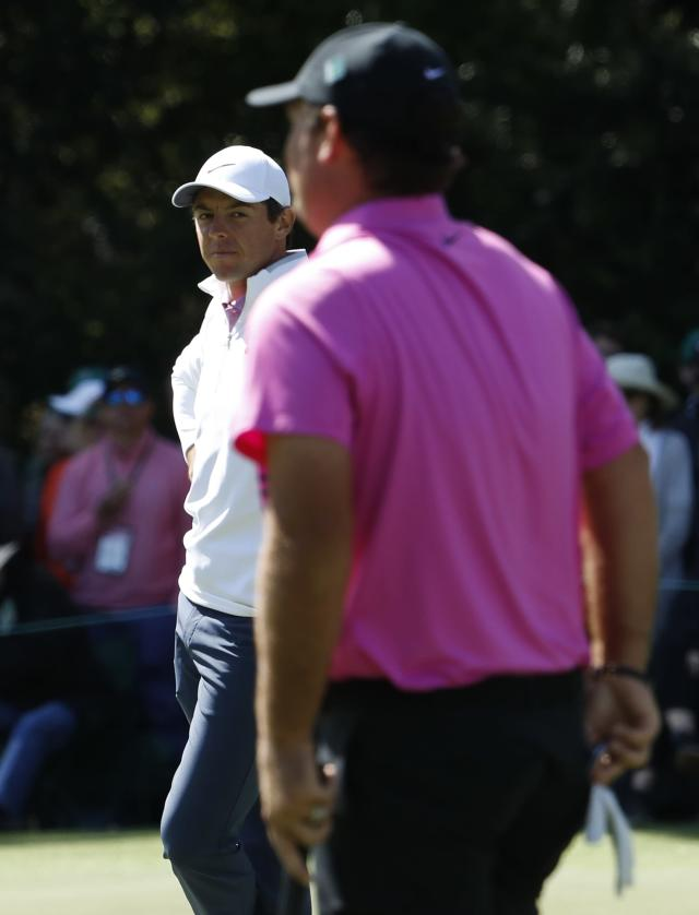 Rory McIlroy of Northern Ireland looks over at Patrick Reed of the U.S. (R) on the 6th green during final round play of the 2018 Masters golf tournament at the Augusta National Golf Club in Augusta, Georgia, U.S. April 8, 2018. REUTERS/Jonathan Ernst