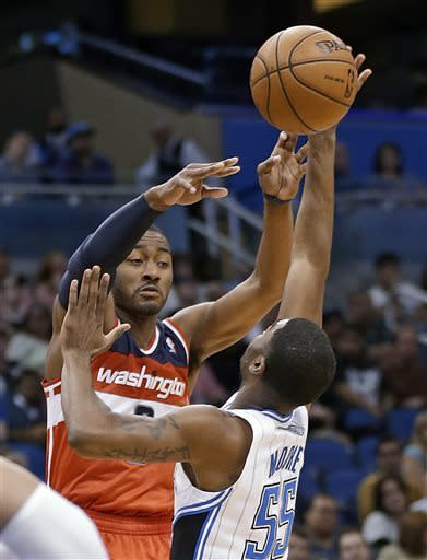 Washington Wizards' John Wall, left, passes the ball over Orlando Magic's E'Twaun Moore (55) during the first half of an NBA basketball game, Friday, March 29, 2013, in Orlando, Fla. (AP Photo/John Raoux)