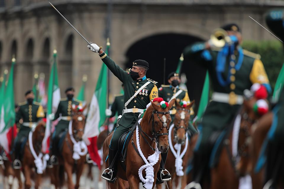 VARIOUS CITIES, MEXICO - SEPTEMBER 16: Soldiers salute towards President Andrés Manuel López Obrador during the Independence Day military parade at Zocalo Square on September 16, 2020 in Various Cities, Mexico. This year El Zocalo remains closed for general public due to coronavirus restrictions. Every September 16 Mexico celebrates the beginning of the revolution uprising of 1810. (Photo by Hector Vivas/Getty Images)
