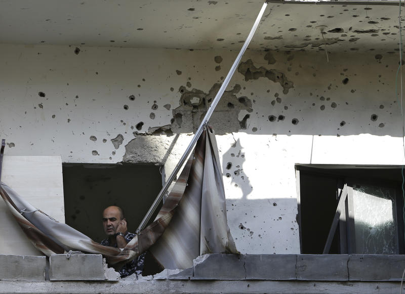 A Lebanese policeman speaks on his phone, as he stands at a damaged balcony where a rocket struck an apartment in a building, at Chiyah district south of Beirut, Lebanon, Sunday May 26, 2013. Rockets slammed Sunday into two Beirut neighborhoods that are strongholds of Lebanon's Hezbollah group, wounding at least 4 people, Lebanese security officials and media said. Tensions have been running high in Lebanon, and Syrian rebels have threatened to retaliate against the militant Shiite Hezbollah group for sending fighters to assist President Bashar Assad's forces in Syria. (AP Photo/Hussein Malla)