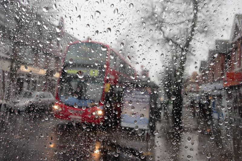 [UNVERIFIED CONTENT] Raindrops on a transparent surface, with an out-of-focus background. Awful british weather in this outdoor scene with torrential rain. A red London bus with its headlights on has stopped to collect passengers at a bus stop. A damp and grey british high street scene. London, UK