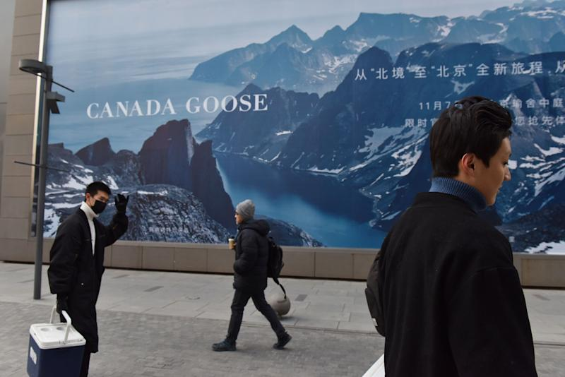People walk past a Canada Goose billboard in Beijing on December 15, 2018. - Canada Goose, the Canadian manufacturer of high-end parkas, postponed the opening of its store in Beijing on December 15, a decision that comes in the midst of a diplomatic crisis over Canada's arrest of the chief financial officer of Chinese telecom giant Huawei. (Photo by GREG BAKER / AFP) (Photo credit should read GREG BAKER/AFP via Getty Images)