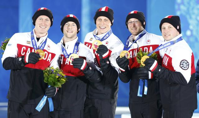 Gold medallists Canada's Brad Jacobs, Ryan Fry, E.J. Harnden, Ryan Harnden and Caleb Flaxey (L-R) celebrate during the victory ceremony for the men's curling event at the 2014 Sochi Winter Olympics in Sochi, February 22, 2104. REUTERS/Shamil Zhumatov (RUSSIA - Tags: SPORT CURLING OLYMPICS)