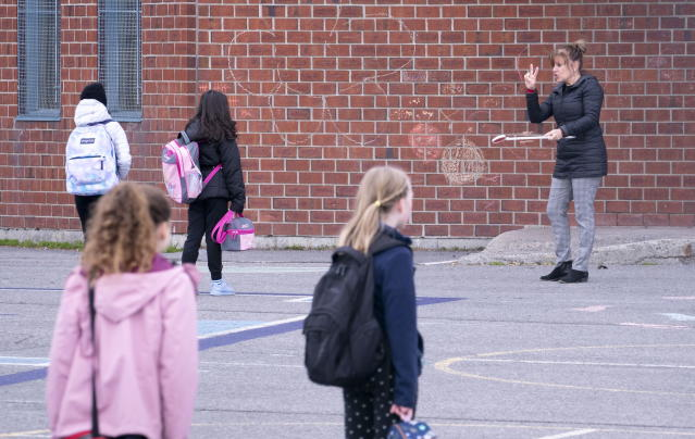 Primary school teacher Celine Guerin explains the 2-metre distancing to her students in the school yard of the Marie-Derome School in Saint-Jean-sur-Richelieu, Que. on Monday, May 11, 2020. Primary schools and daycares outside of the greater Montreal area gradually open Monday. THE CANADIAN PRESS/Paul Chiasson