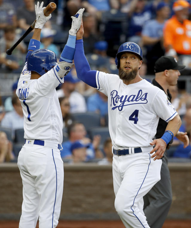 Kansas City Royals' Alex Gordon (4) celebrates with Ryan Goins (1) after scoring on a double by Hunter Dozier during the second inning of a baseball game against the Texas Rangers Wednesday, June 20, 2018, in Kansas City, Mo. (AP Photo/Charlie Riedel)
