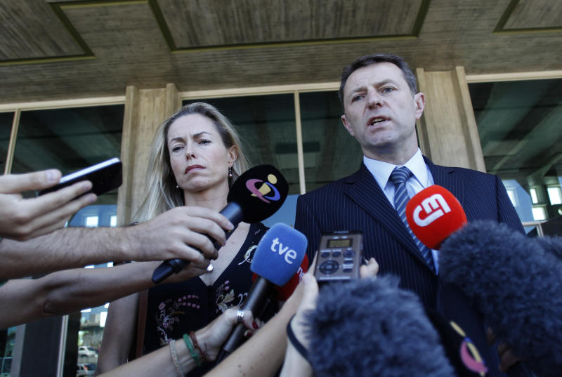 Kate McCann, left, and Gerry McCann, the parents of missing British girl Madeleine McCann, talk to the media outside a court in Lisbon, Tuesday, July 8, 2014. The couple traveled to Lisbon to testify in their libel action against former Portuguese detective Goncalo Amaral who published a book about Madeleine's disappearance. (AP Photo/Francisco Seco)