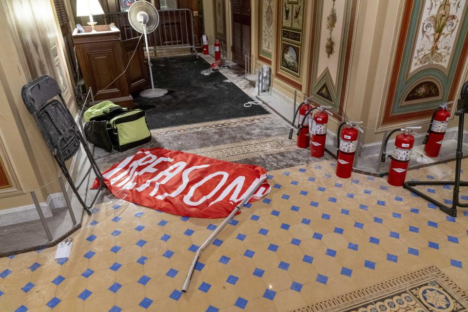 """A flag that reads """"Treason"""" is visible on the ground in the early morning hours of Thursday, Jan. 7, 2021, after protesters stormed the Capitol in Washington, on Wednesday. (AP Photo/Andrew Harnik)"""
