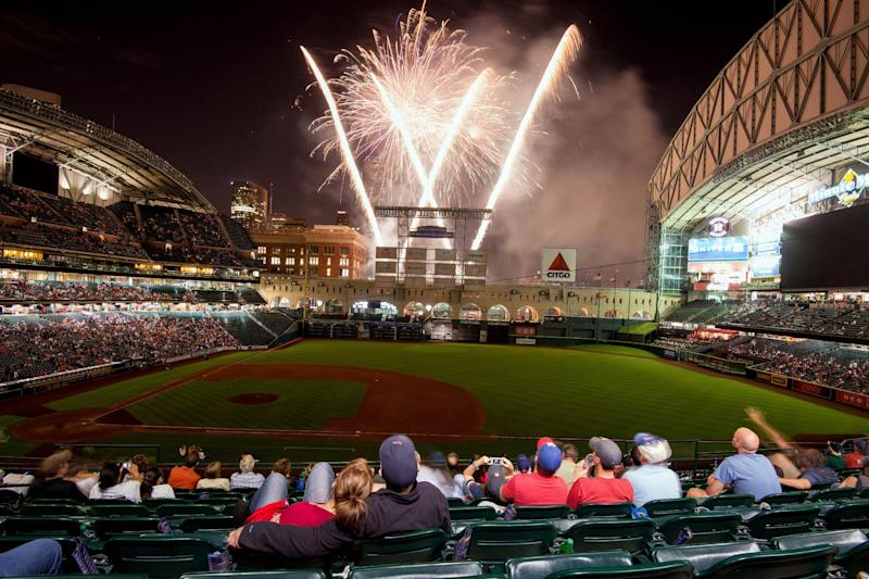 Melissa Bull and Byron Wilcher watch as fireworks explode following the Houston Astros' 8-2 win over the Texas Rangers in a season-opening baseball game at Minute Maid Park, Sunday, March 31, 2013, in Houston. (AP Photo/Houston Chronicle, Smiley N. Pool)