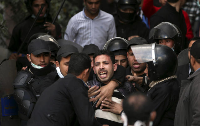 Egyptian riot police arrest a man during clashes with protesters near Tahrir Square in Cairo, Egypt, Wednesday, Jan. 30, 2013. Egypt's liberal opposition leader called for a broad national dialogue with the Islamist government, all political factions and the powerful military on Wednesday, aimed at stopping the country's eruption of political violence that has left scores dead in the past week. (AP Photo/Khalil Hamra)