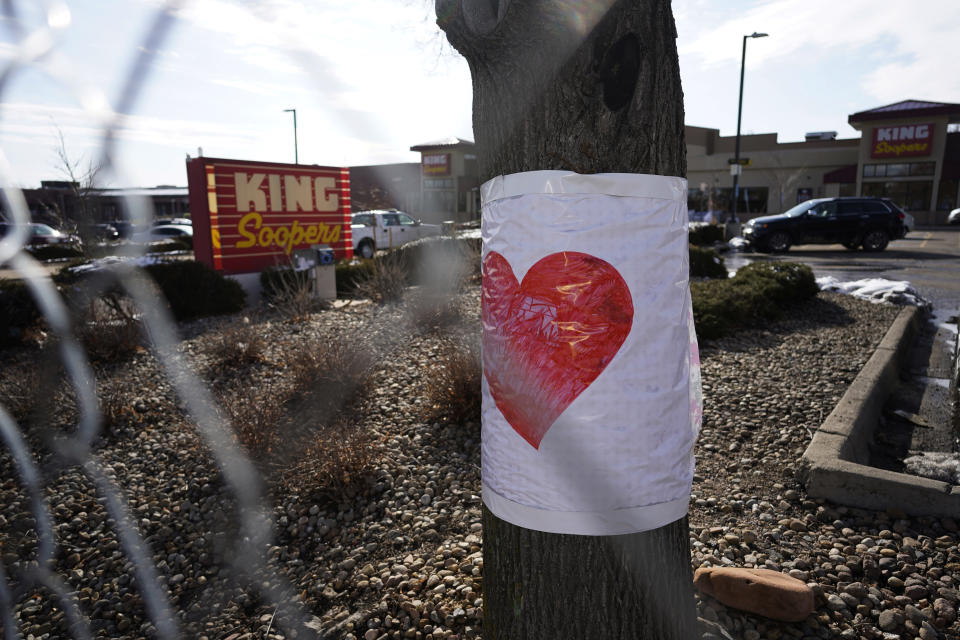 A drawig of a heart is wrapped on a tree behind the makeshift fence put up around the parking lot outside a King Soopers grocery store where a mass shooting took place Tuesday, March 23, 2021, in Boulder, Colo. (AP Photo/David Zalubowski)