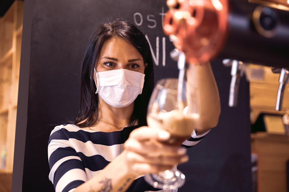 Bartender serves a fresh beer in a pub in the pandemic days, wearing protective face mask.