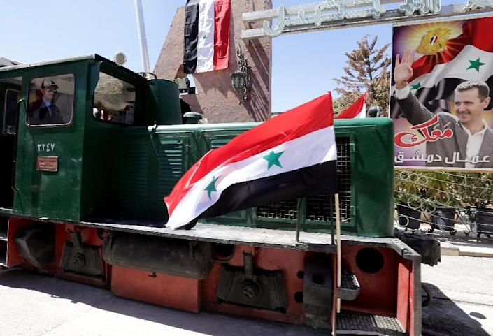 A conductor drives a tourist train flying Syrian flags in Damascus, after the rail route for the train between two neighbourhoods in the Syrian capital Raboeh and Dumar re-opened on May 1, 2015 (AFP Photo/Louai Beshara)