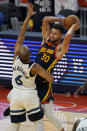 Golden State Warriors guard Stephen Curry (30) looks to pass the ball while defended by Minnesota Timberwolves guard Jordan McLaughlin (6) during the first half of an NBA basketball game in San Francisco, Wednesday, Jan. 27, 2021. (AP Photo/Jeff Chiu)