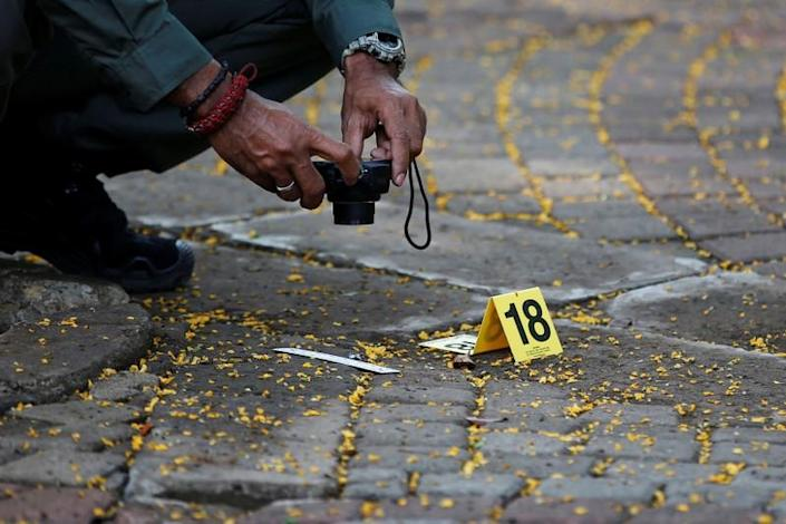 An Indonesian forensic policeman takes pictures of evidence of a blast at National Monument (Monas) complex in Jakarta