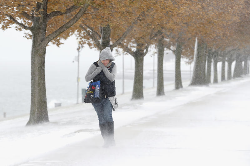 A woman walking the half mile from Chicago's Adler Planetarium to the Chicago Aquarium braces herself in the stiff wind and blowing snow off Lake Michigan, Monday, Nov. 11, 2019, in Chicago. (AP Photo/Charles Rex Arbogast)
