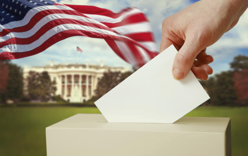 Hand putting a voting ballot into the box with US flag and the White House on the background