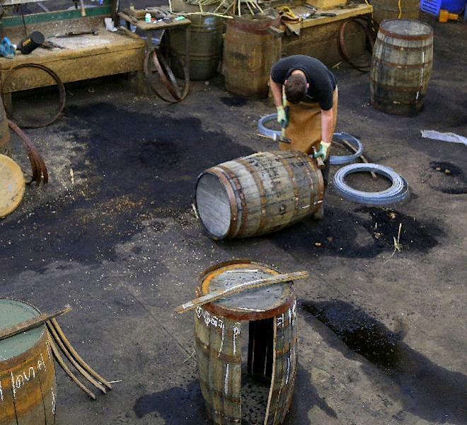 In this photo taken June 28, 2016, a worker at the cooperage of the Balvenie distillery in Dufftown, in the Speyside region of Scotland, works on a whisky barrel. The distillery also has a working malting floor and offers tours and tastings. (Michelle Locke via AP)